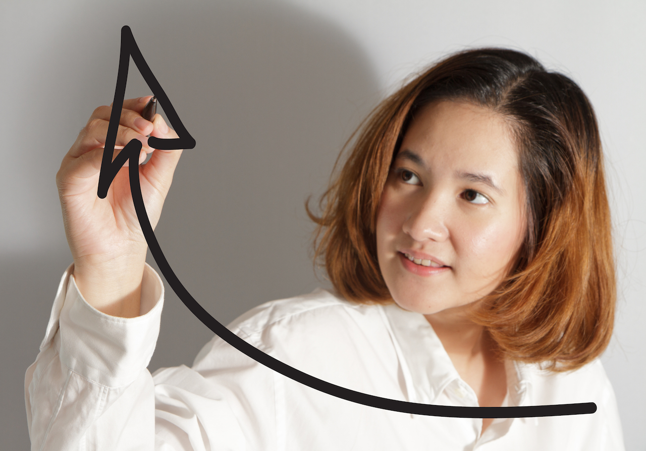 Businesswoman drawing a rising arrow, representing business growth