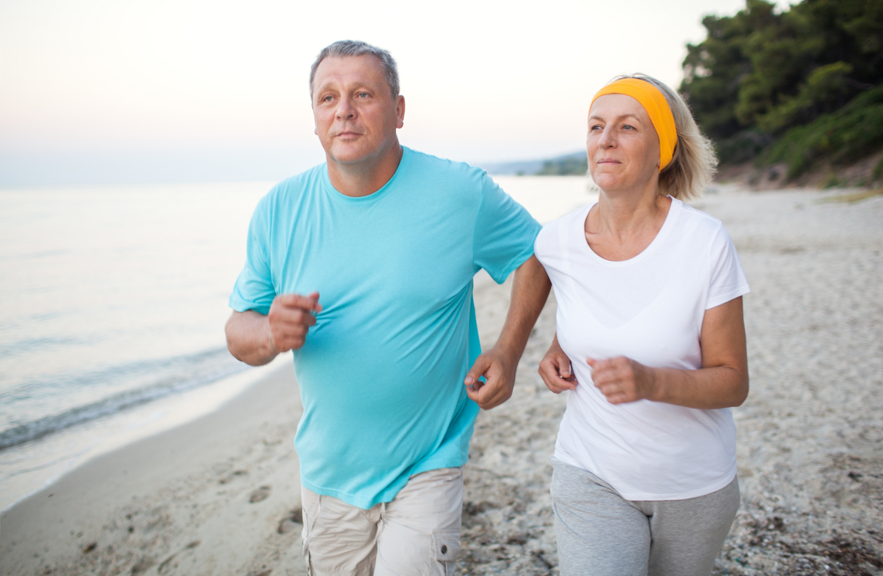 Senior man and woman having a run along the shore. Scene with sea, sand and trees. Healthy and active way of life